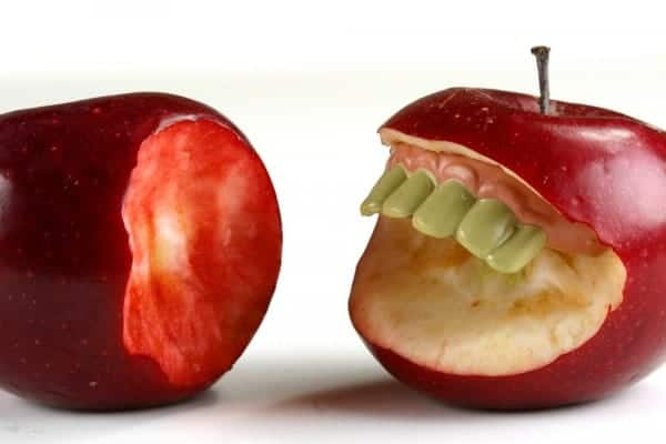 Apple with teeth biting another apple