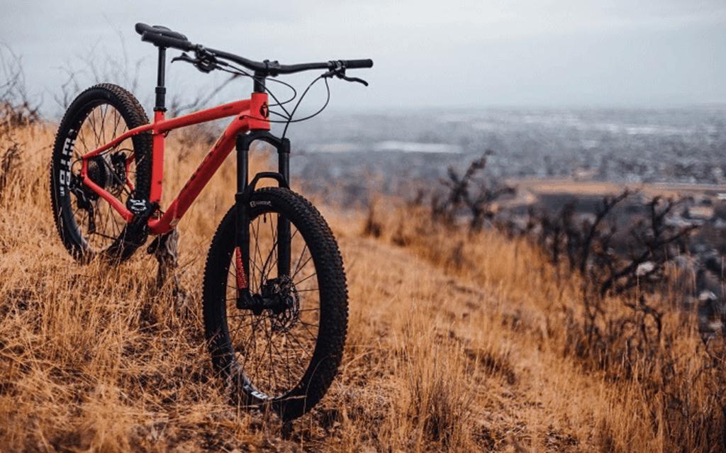 orange mountain bike parked up on hill